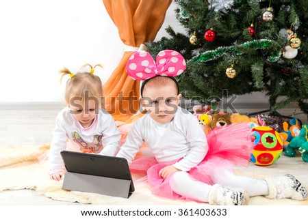 Children, little girls are looking at the plate near the Christmas tree - stock photo