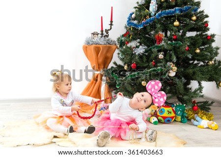 Children, little girls stretch beads near a Christmas tree - stock photo