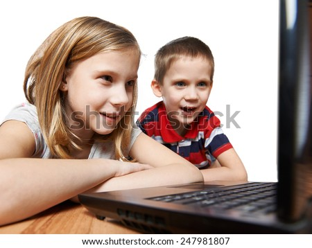 Children looking to laptop lying on the floor - stock photo