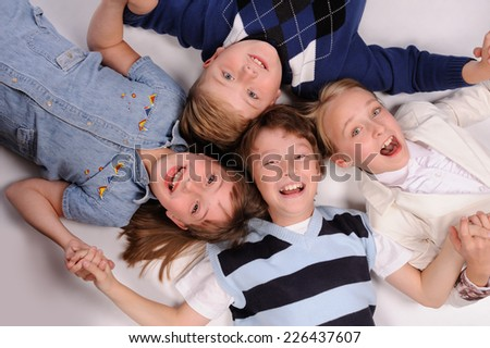 children lying on the floor isolated over white background - stock photo