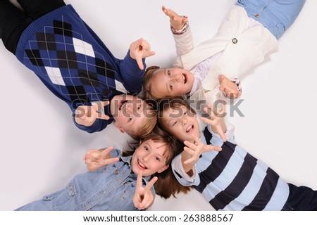 children lying on the floor isolated over white background - stock photo