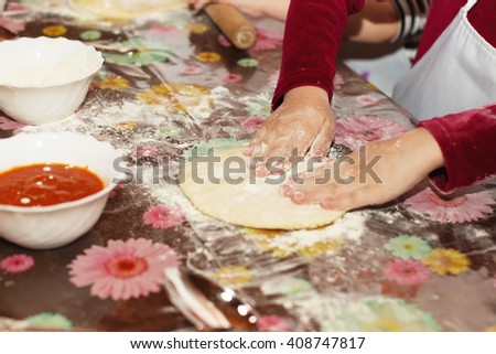 Children make pizza. Master class for children on cooking Italian pizza. Young children learn to cook a pizza. Kids preparing homemade pizza - stock photo