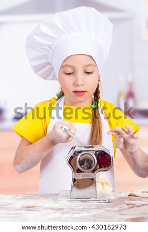 Children make the dough in the kitchen, roll a rolling pin, make the noodles - stock photo