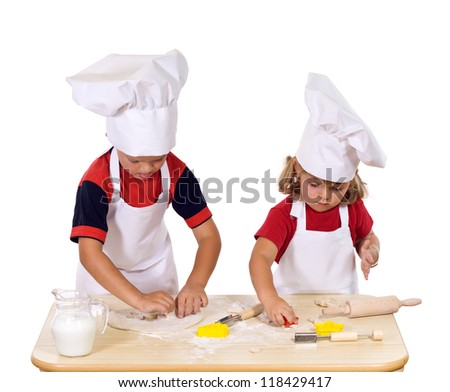 Children making christmas cookies dressed as chefs - cutting the dough to star and pine tree shapes - stock photo