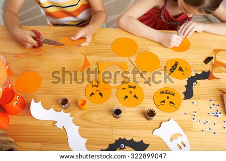 Children making Halloween decorations from colored paper - stock photo