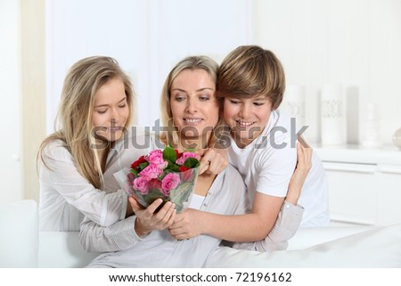 Children offering bunch of flowers on mother's day - stock photo