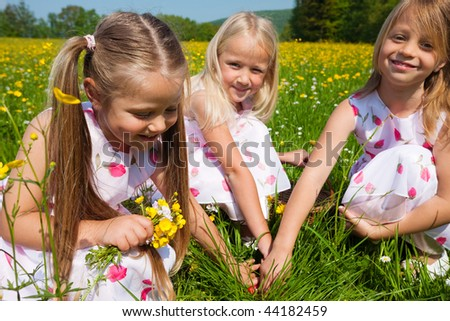 Children on a beautiful sunlit meadow in spring on an Easter egg hunt having just found a nest - stock photo