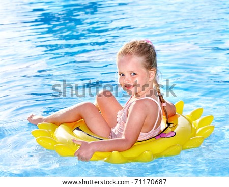 Children  on inflatable ring in swimming pool. - stock photo