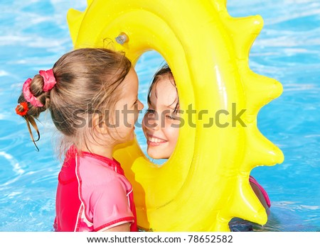 Children  on inflatable ring in swimming pool - stock photo