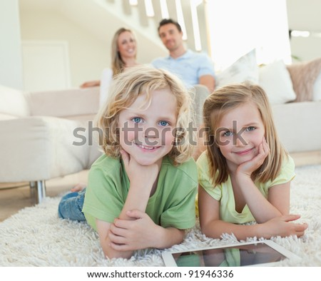 Children on the carpet together with tablet and parents behind them - stock photo