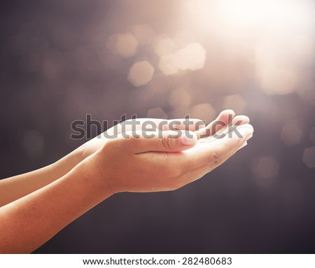Children open empty hands with palms up over blurred beautiful bokeh of candle light on sunrise background. Vintage style. - stock photo