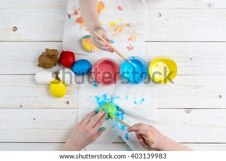 Children paint eggs for Easter on a wooden table top view - stock photo