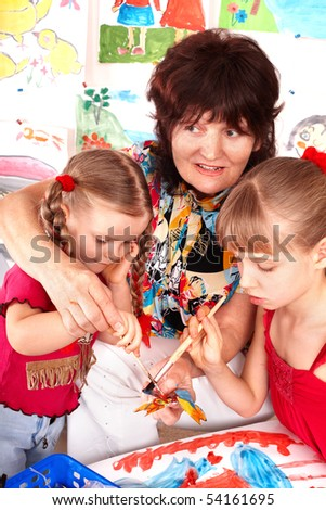 Children  painting with teacher. Preschool. - stock photo