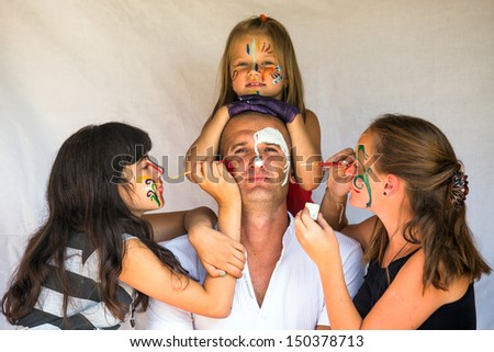 Children paints face of his father (Happy family concept) - stock photo