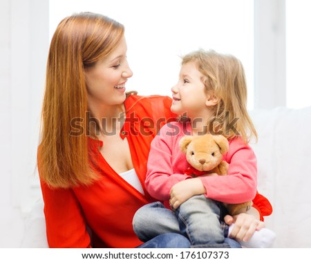 children, parenthood and happiness concept - happy mother and child with teddy bear at home - stock photo