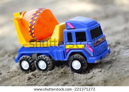 Children plastic machine in the sandbox. Toy Machine-mixer - stock photo