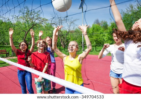 Children play actively near the volleyball net on the court during sunny summer day outside - stock photo