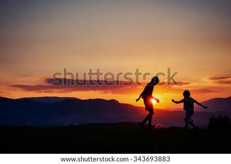 Children playing at sunset - stock photo