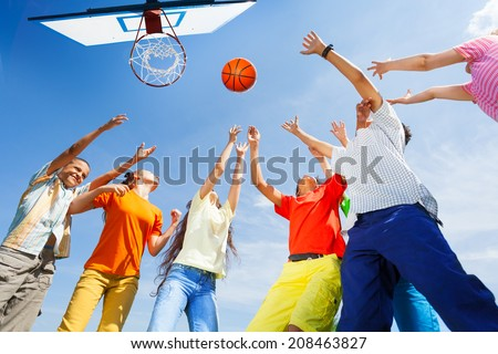 Children playing basketball with a ball up in sky - stock photo