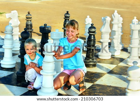 Children playing big chess outdoor. - stock photo