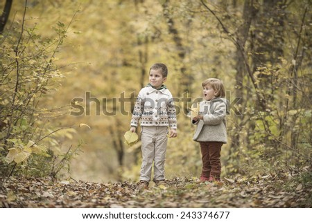 Children playing in a forest with yellow leaves - stock photo