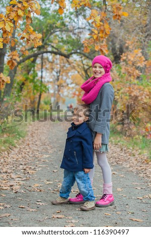 Children playing in autumn park. Kids outdoor games. - stock photo