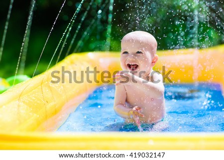 Children playing in inflatable baby pool. Kids swim and splash in colorful garden play center. Happy little boy playing with water toys on hot summer day. Family having fun outdoors in the backyard. - stock photo