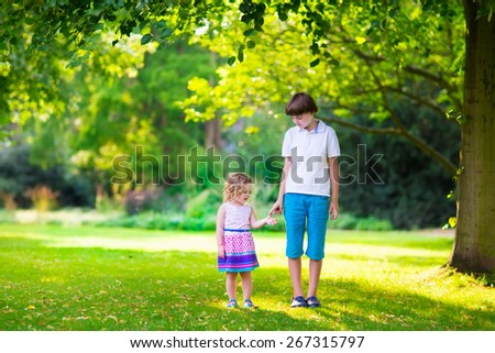 Children playing in park. Holding hands walking in forest. Happy cute little girl in colorful  dress and laughing brother, teenage boy, running together playing in park on beautiful warm summer day - stock photo