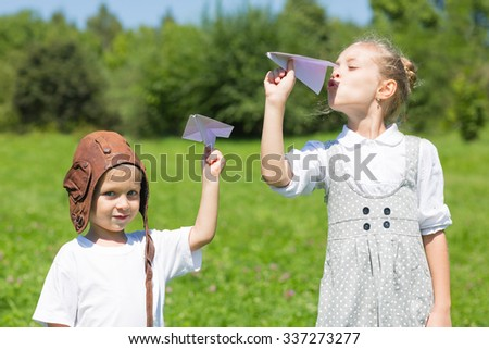Children playing in the park paper airplanes. Brother and sister. Series of images. - stock photo
