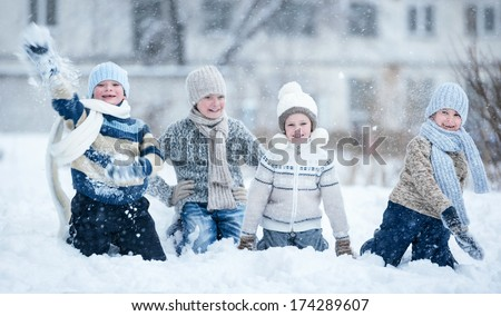 Children playing in the snow on a winter day - stock photo