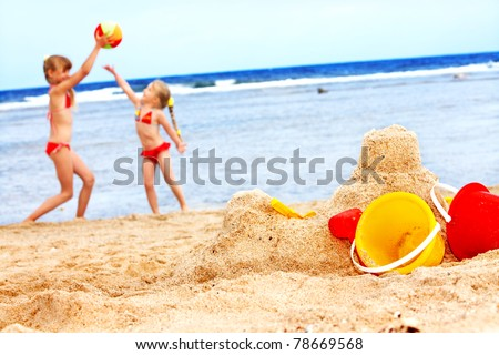 Children  playing on  beach with ball. - stock photo