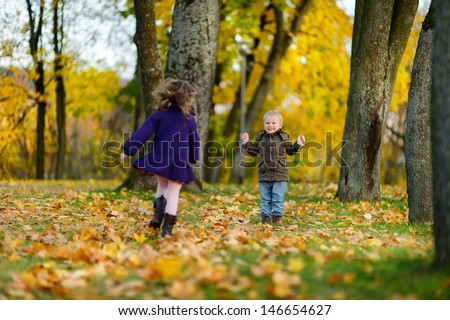 Children playing on beautiful autumn day - stock photo