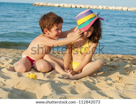 Children playing on the beach with a hat - stock photo