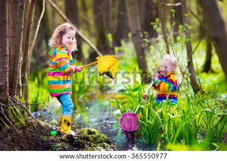Children playing outdoors. Preschool kids catching frog with net. Boy and girl fishing in forest river. Adventure kindergarten day trip into wild nature, young explorer hiking and watching animals. - stock photo