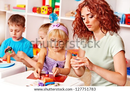 Children playing plasticine in kindergarten. - stock photo