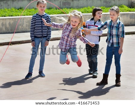 Children playing skipping rope jumping game and laughing outdoors - stock photo