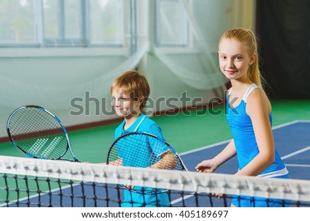 Children playing tennis and posing indoor - stock photo
