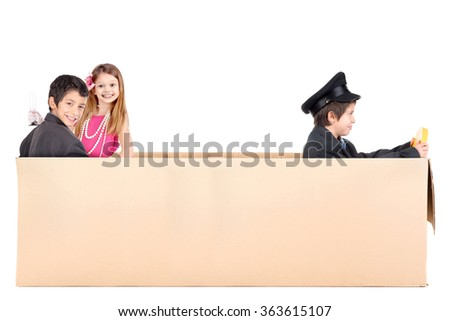 Children playing VIP people in a cardboard box limousine - stock photo