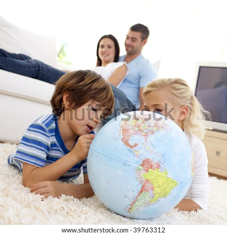 Children playing with a terrestrial globe in living-room with their parents on sofa - stock photo