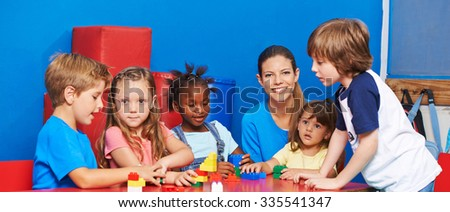 Children playing with building bricks in child care with nursery teacher - stock photo