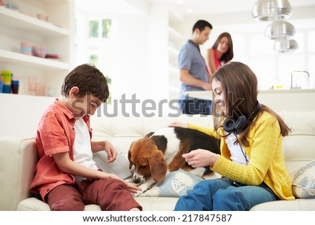 Children Playing With Dog On Sofa As Parents Make Meal - stock photo