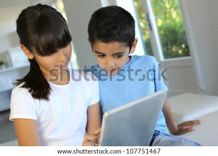 Children playing with electronic tablet at home - stock photo