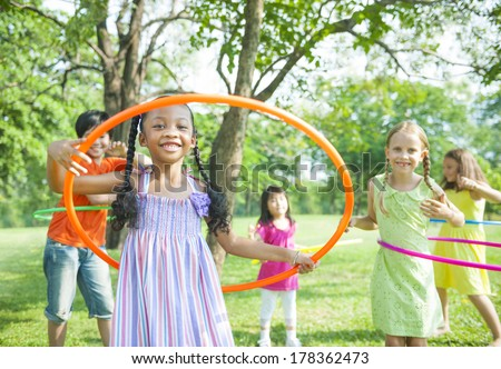 Children Playing with Hula Hoops in Park - stock photo
