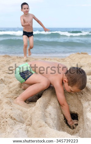 Children playing with  sand on a beach, digging hole, ocean or sea with waves in the background. - stock photo