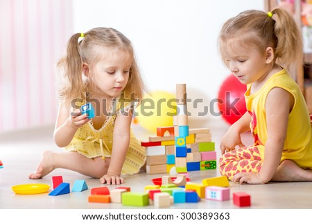 children playing wooden toys at home or kindergarten - stock photo