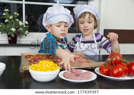 Children preparing pizza at kitchen - stock photo