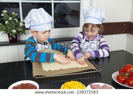 Children preparing pizza at kitchen. - stock photo