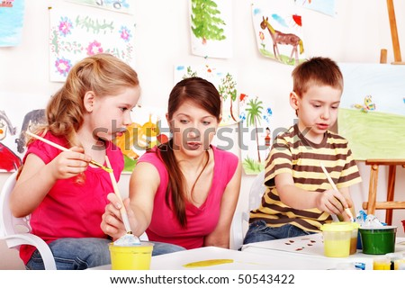 Children preschooler  with teacher draw paints in play room. Child care. - stock photo