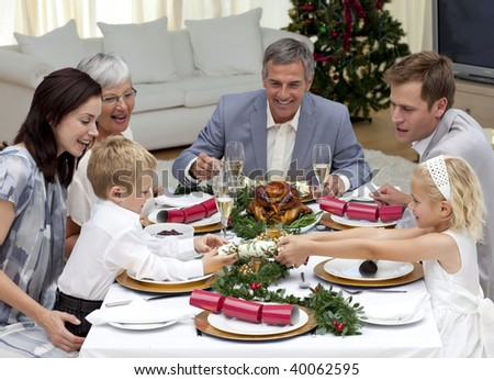 Children pulling a Christmas cracker at home in a family dinner - stock photo