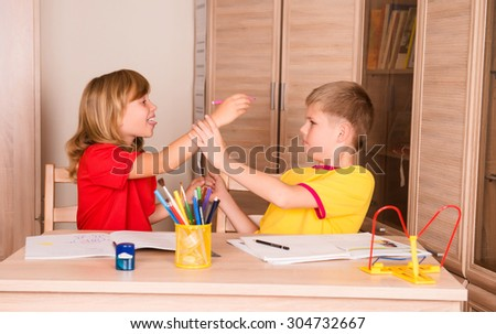 Children quarreling. Sister teasing brother while doing homework together.  - stock photo